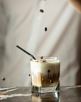 Бармен окропляет кофейные зерна кофейным напитком со льдом