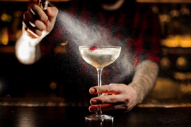 Bartender sprinkling bitter on the elegant cocktail glass
