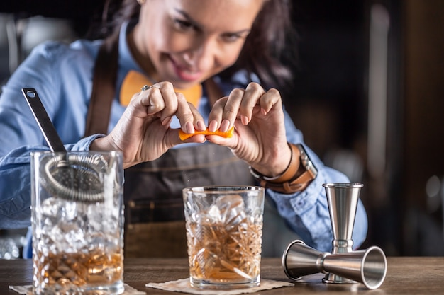 Bartender squeezes orange into an old fashioned cocktail with whiskey in an ornamental glass.