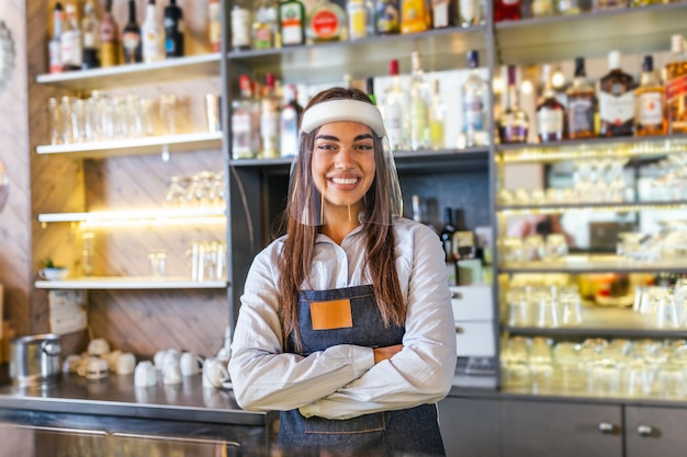 Bartender standing at the counter while wearing face shield