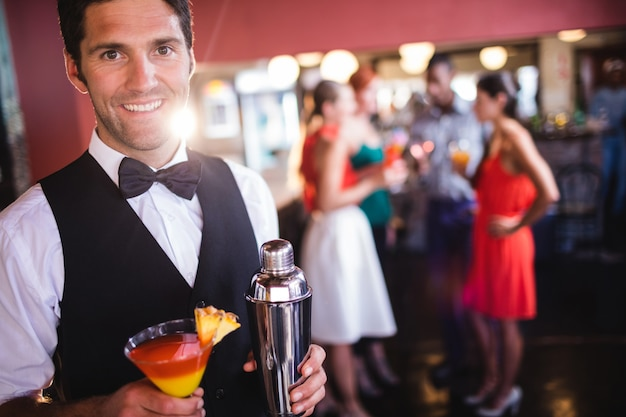 Bartender standing with cocktail glass and cocktail shaker in nightclub