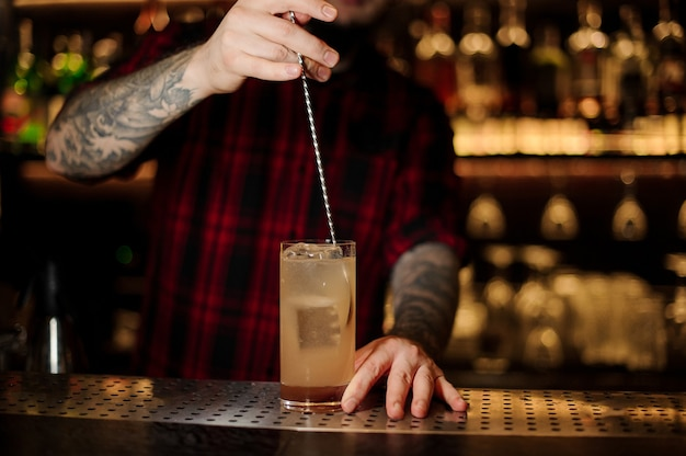 Bartender stirring a lemonade cocktail with the spoon in the glass on the bar counter