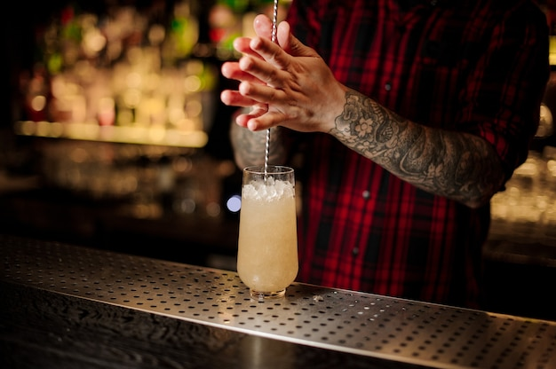 Bartender stirring a trinidad swizzle cocktail with the spoon in the glass on the bar counter