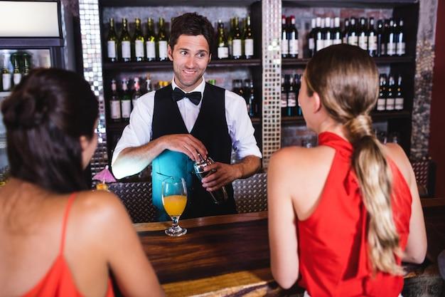 Bartender talking with customer at bar counter