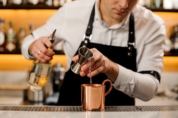 Bartender in white shirt pouring a portion of alcoholic drink into a cup