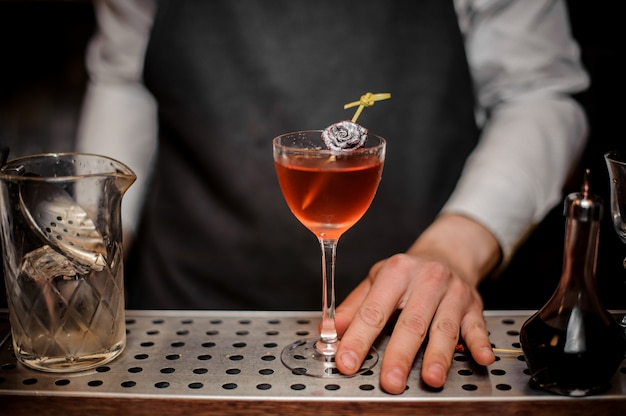 夏の飲み物で満たされたカクテルグラスを持つバーテンダー