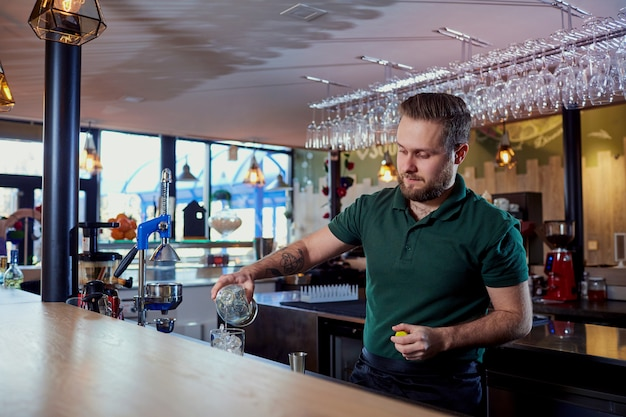 The bartender with beard behind bar pours a drink into  glass