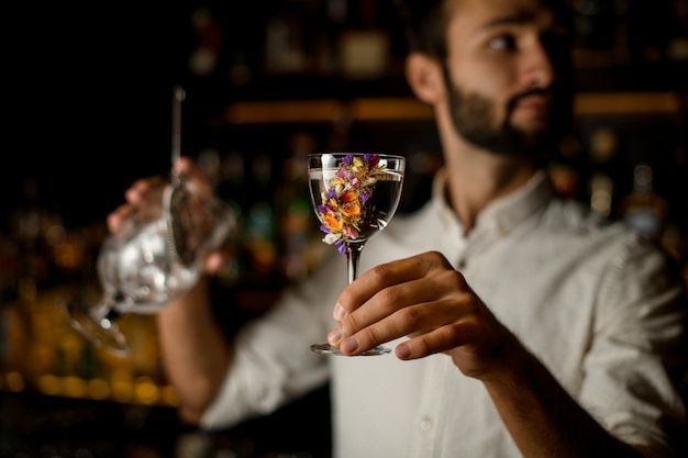 Bartender with beard holds an alcohol and strainer in glass