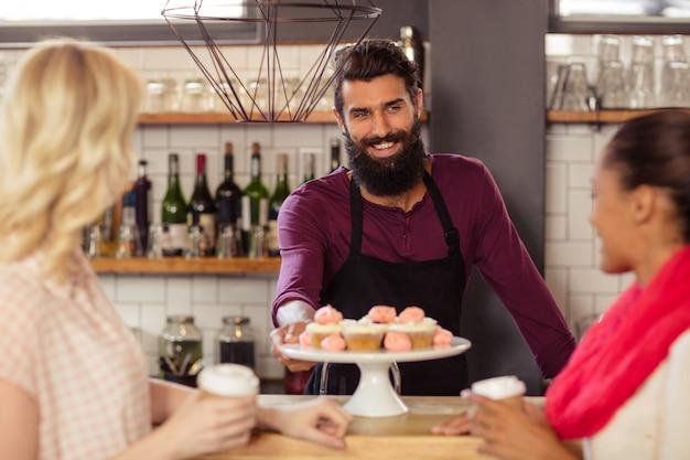 一杯のコーヒーを保持している顧客とバーテンダー