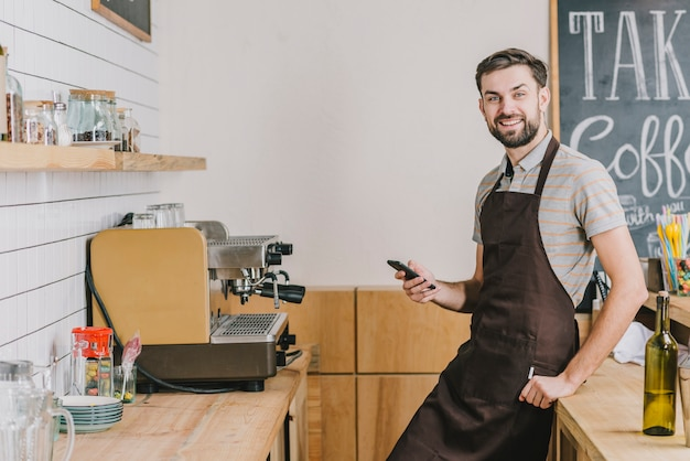 Bartender with smartphone looking at camera