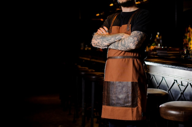 Bartender with tattoo on hands dressed in brown apron