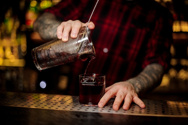 Bartender with tattoos pouring fresh strong alcoholic cocktail into a glass on bar against the bright lights