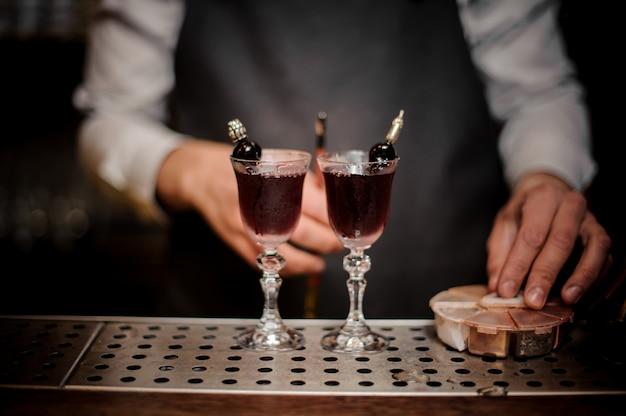 甘い夏のアルノーカクテルで満たされた2つのエレガントなグラスを持つバーテンダー