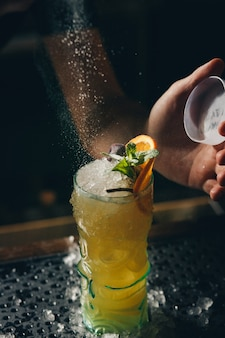Bartenders hands sprinkling the juice into the cocktail glass filled with alcoholic drink