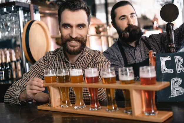 Bartenders pour fresh beer into glasses in pub