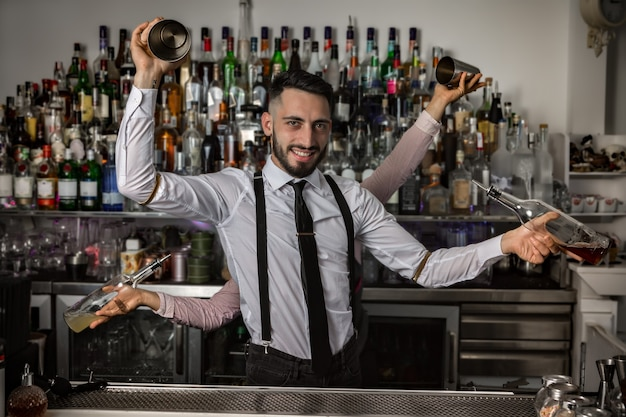 Bartenders with shakers and bottles in pub