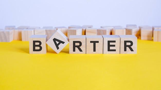 Бартерное слово состоит из деревянных строительных блоков, лежащих на желтом столе, концепция