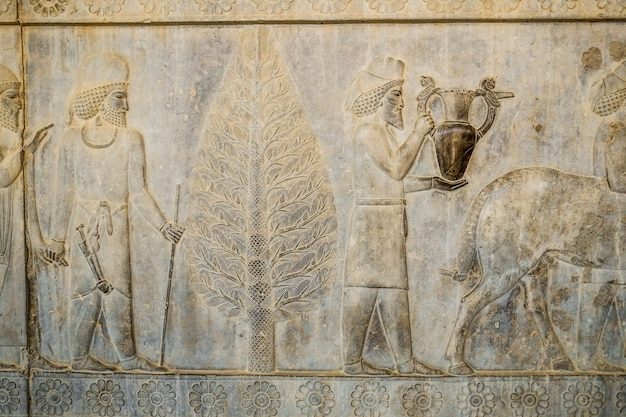 A bas-relief depiction of tribute bearers carry present for the king at persepolis, iran.