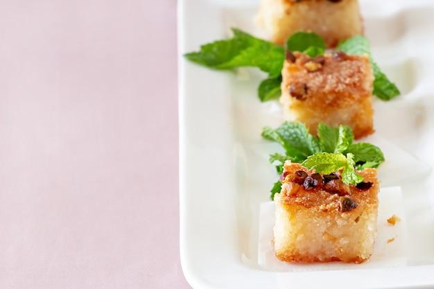 Три пирожные basbousa или namoora традиционный арабский десерт. очень вкусный домодельный торт манной крупы с гайками на белой плите.