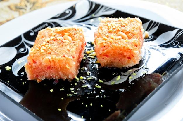 Пирог basbousa с макросом миндаля в форме для выпечки на столе. горизонтальная. арабская еда.