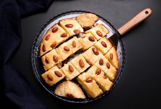 セモリナ粉とアーモンドのバスブアラビアパイは、黒い背景に粉々にカット