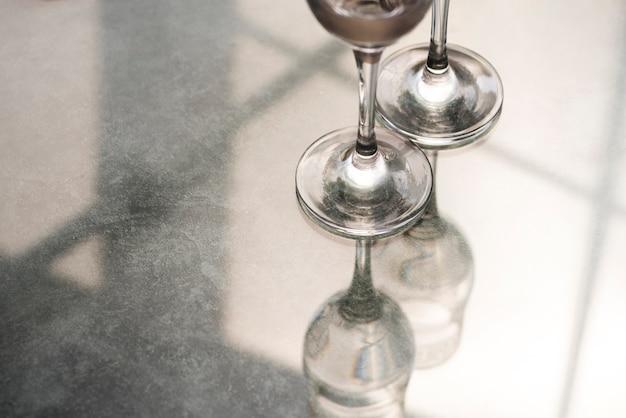 Base of champagne glasses on reflective desk