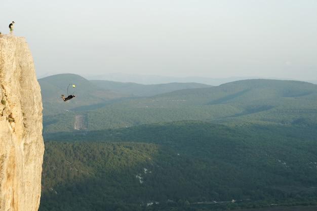 崖から飛び降りるベースジャンパー