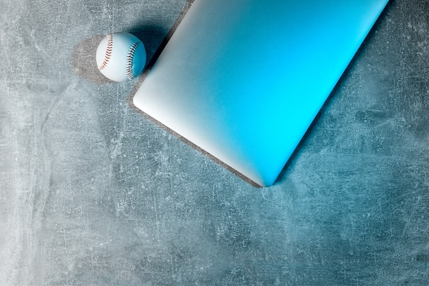 Baseball ball and grey laptop on grey background. online workout concept