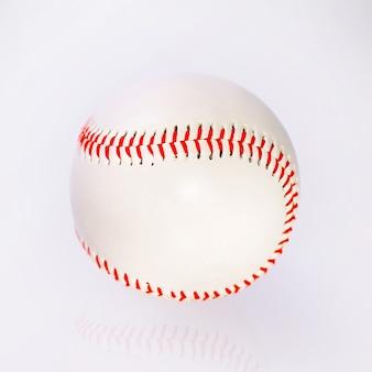 反射のあるテーブルの上の赤いファームウェアの野球ボール