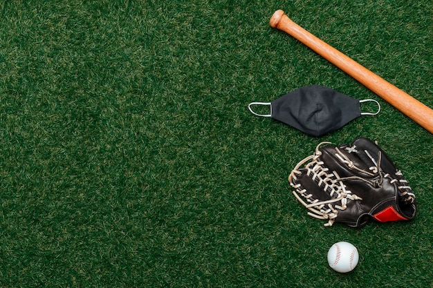 Baseball bat, ball, glove and mask isolated on a field of grass