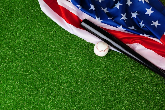 Baseball bat and ball with american flag on grass Premium Photo