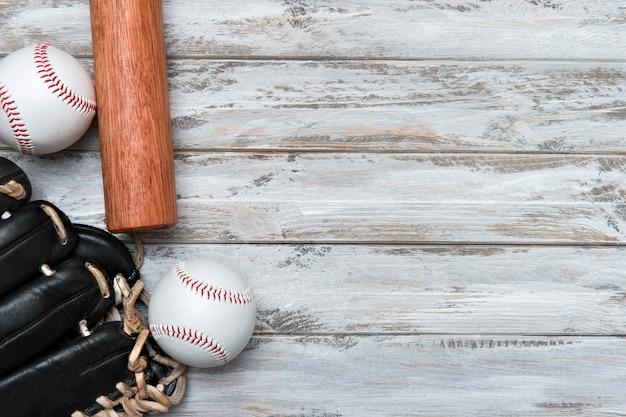 木製の背景に野球のバット、グローブ、ボール
