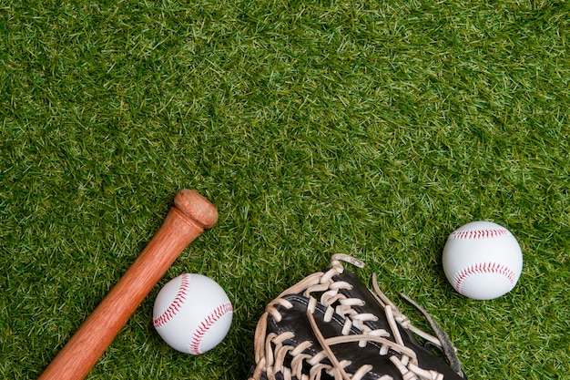 Baseball bat, glove and ball on green grass field