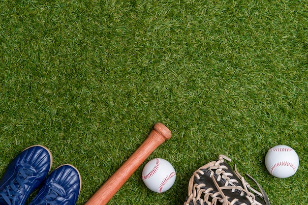 Baseball bat,shoes, glove and ball on green grass field