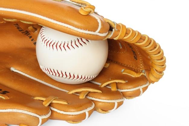 白で隔離されるボールと野球キャッチャーミットをクローズアップ
