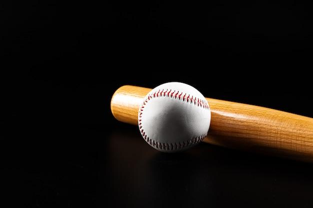 Baseball game equipment on dark black background close up