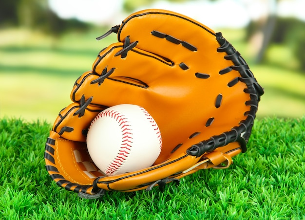 Baseball glove and ball on grass in park