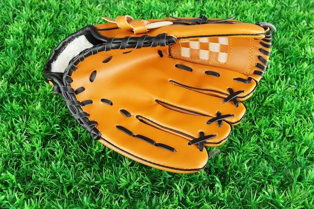 草の背景に野球のグローブ