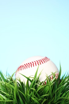 Baseball in grass on blue