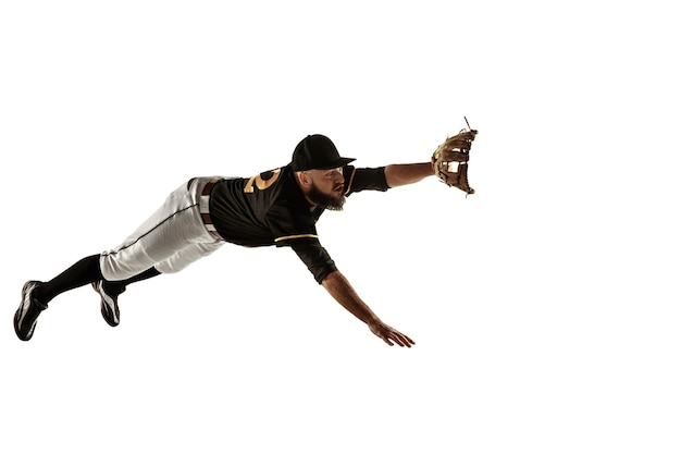 Baseball player in a black uniform practicing on a white background.