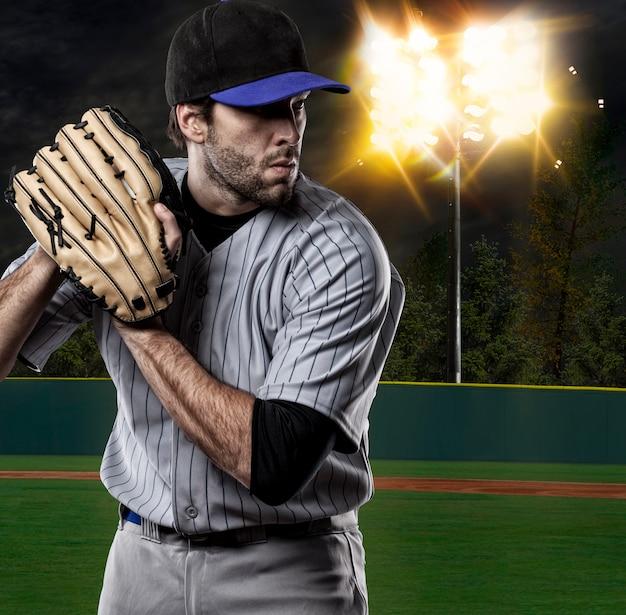 Baseball player on a blue uniform on baseball stadium.