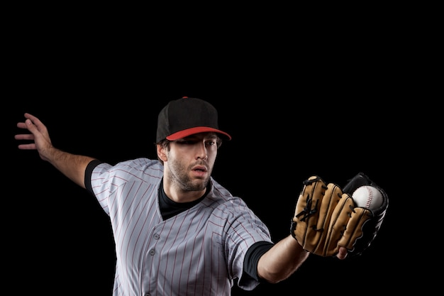 Baseball player catching a ball on a black background. studio shot.