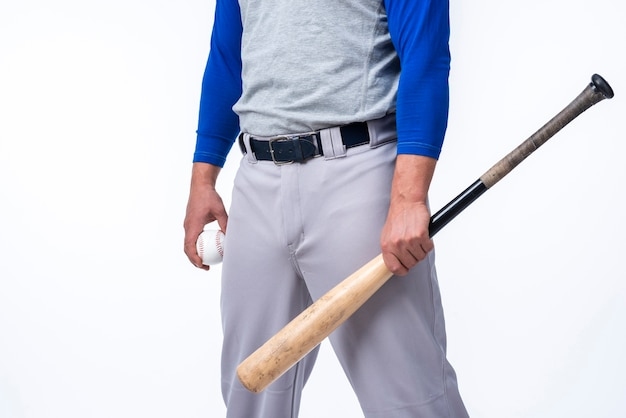 Baseball player holding bat and ball