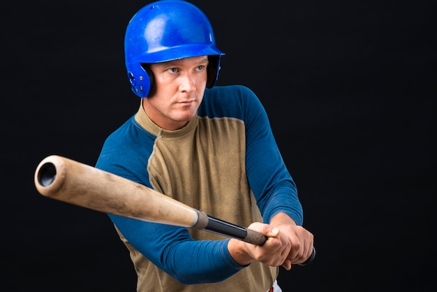 Baseball player holding bat and looking away