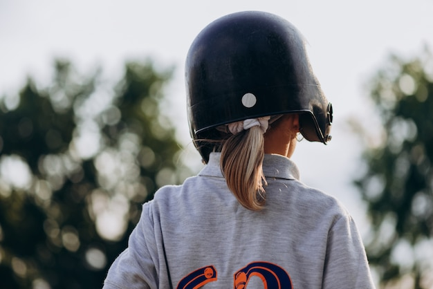 Baseball player in a painless helmet turns her back to the camera