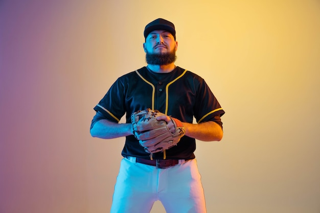 Baseball player, pitcher in a black uniform practicing and training on gradient background in neon light