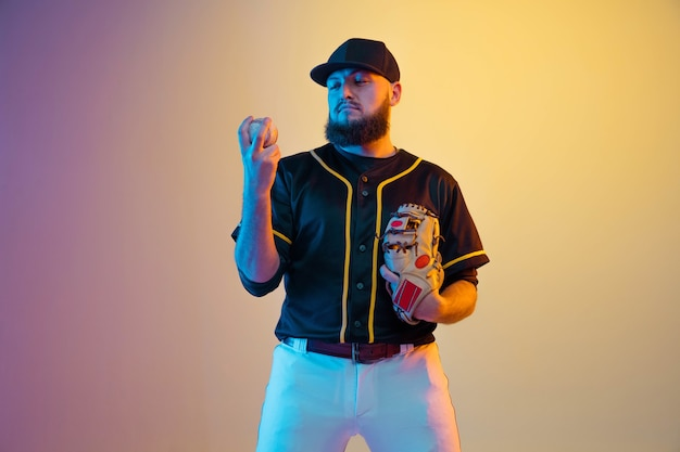 Baseball player, pitcher in a black uniform practicing and training on gradient wall in neon light. young professional sportsman in action and motion. healthy lifestyle, sport, movement concept.