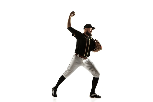 Baseball player, pitcher in a black uniform practicing and training isolated on a white wall. young professional sportsman in action and motion. healthy lifestyle, sport, movement concept.