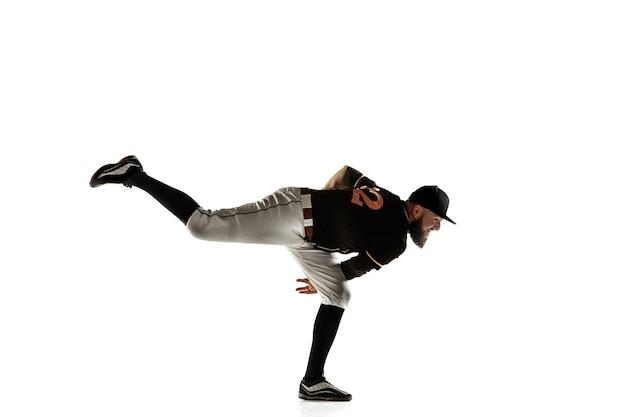野球選手、白い壁に隔離された練習とトレーニングの黒いユニフォームを着た投手。アクションと動きの若いプロスポーツマン。健康的なライフスタイル、スポーツ、運動の概念。