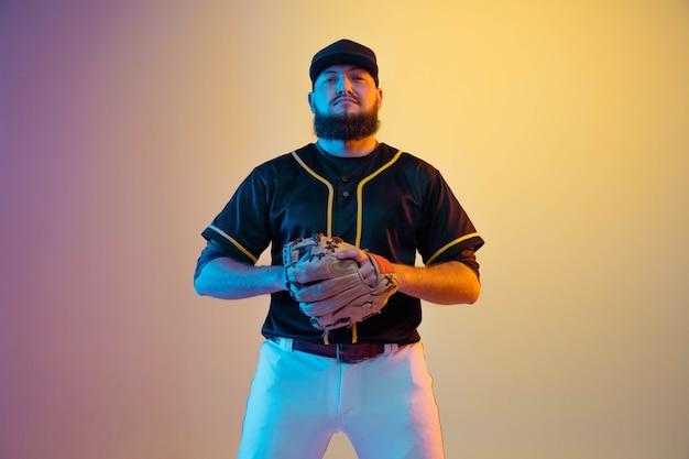 ネオンの光の中でグラデーションの背景に練習とトレーニングをする野球選手、黒いユニフォームを着た投手